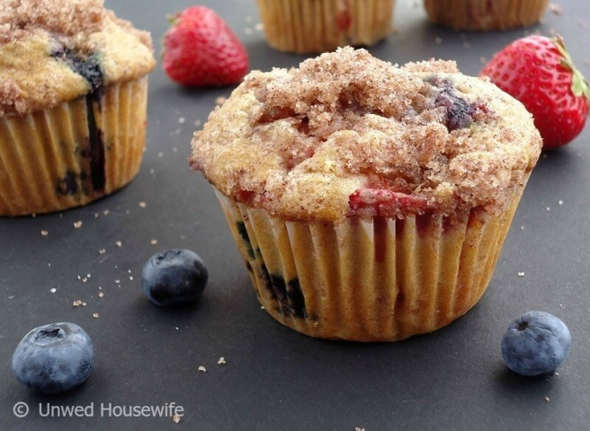Strawberry Blueberry Muffins   Unwed Housewife   Big, bakery style muffins made with fresh strawberries and blueberries and topped with a cinnamon sugar crumble. One-of-a-kind strawberry blueberry muffin recipe.